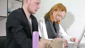 Young businessman and woman working in the office. Woman is writing some notices on a paper. Man is tapping on a laptop keyboard stock video footage