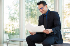 Young businessman at work. Portrait of a young Hispanic businessman reviewing some documents at work and smiling Stock Image