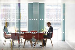 Young businessman working alone in an office meeting room royalty free stock image