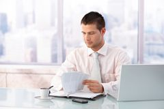 Young businessman working in bright office Royalty Free Stock Photo