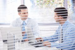 Young businessman working in bright office Stock Photos