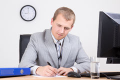 Young businessman working in bright office Royalty Free Stock Image