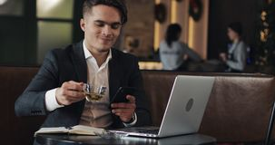 Young businessman working in cafe. Freelancer using smartphone and laptop. Successful busines, IT, Freelancer concept. stock video footage