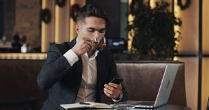 Young businessman working in cafe. Freelancer using smartphone and laptop. Successful busines, IT, Freelancer concept. stock video