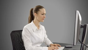 Young businessman working on computer at desk. Young beautiful businesswoman typing on a computer and talking on the phone. stock footage