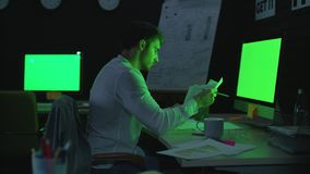 Young businessman working on computer with green monitor in night office. Pensive business analyst checking financial reports in dark office. Concentrated man stock video footage
