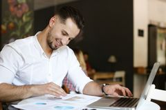 Young businessman working with documents and laptop at cafe. royalty free stock image