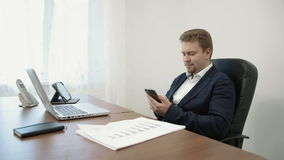 Young businessman working in his office in front of the laptop computer. He uses his smarphone touching the screen with. In this stock footage you can see young stock video