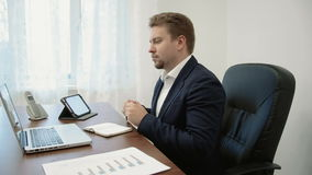 Young businessman working in his office in front of the laptop computer. He writes something down in his notebook. In this stock footage you can see young stock video