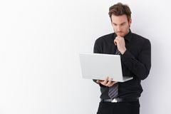 Young businessman working on laptop. Handsome young businessman working on laptop, standing over white background Stock Photo