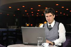 Young businessman working on laptop. Happy young man sitting relaxed and working on computer at luxury cafee restaurant Stock Photography