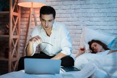 Young businessman working on laptop in bed with young woman. Young woman is sleeping. stock image