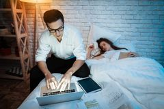Young businessman working on laptop in bed with young woman. Young woman is sleeping. stock photography