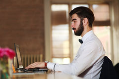 Young businessman working at a laptop in office Stock Photography