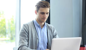 Young businessman working with laptop at office. Stock Photos