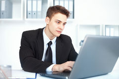 Young businessman working on laptop in office Stock Photography