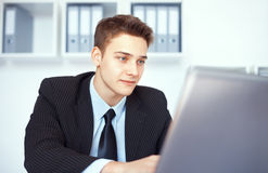 Young businessman working on laptop in office Stock Photos