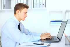 Young businessman working on laptop in office Royalty Free Stock Image