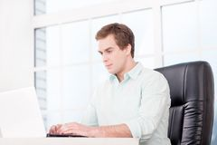 Young businessman working with laptop in office Stock Images