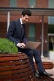 Young businessman working on laptop outside the office Royalty Free Stock Photos