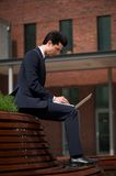 Young businessman working on laptop outside the office Royalty Free Stock Photo