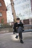 Young businessman working on laptop while sitting on bench Stock Photography