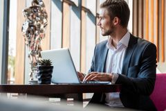 Young businessman working on laptop, sitting in hotel lobby waiting for someone. Young businessman working on laptop, sitting in hotel lobby waiting for someone royalty free stock photo