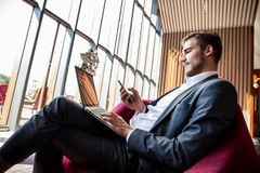 Young businessman working on laptop, sitting in hotel lobby waiting for someone. Young businessman working on laptop, sitting in hotel lobby waiting for someone royalty free stock photos