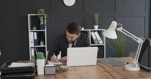 Businesswoman using laptop and taking notes. Young businessman working on laptop and taking notes at office stock video footage