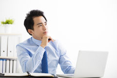 Young businessman working on laptop and thinking Royalty Free Stock Images