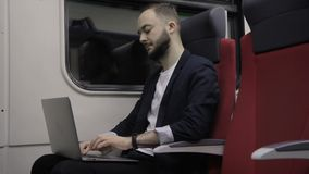 Young businessman is working with laptop and traveling by train. Successful person does work in business trip while sitting in car. Handsome guy types text stock video footage