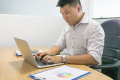 Young businessman working on laptop at workplace royalty free stock image