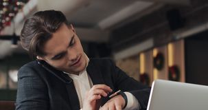 Young businessman working in modern office or co-working, speaks by phone and using smart watch. Successful businessman stock video