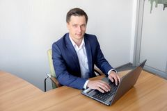 Young man working in office, sitting at desk, looking at laptop computer screen. Royalty Free Stock Photo