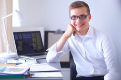 Young businessman working in office, sitting near Stock Photos
