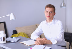 Young businessman working in office, sitting near Royalty Free Stock Images