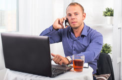 Young businessman working in office, sitting at a table, looking straight and talking on the phone Stock Image