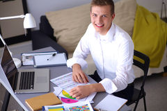 Young businessman working in office, standing near Stock Image
