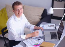 Young businessman working in office, standing near Stock Photography