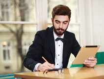 Young businessman working in office with tablet Stock Images