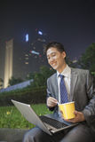 Young businessman working outdoors and eating Stock Image
