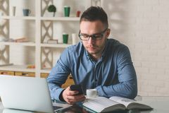 Young businessman working on project. Portrait of young businessperson working on project and using smartphone in modern office. Occupation, work, online Stock Images