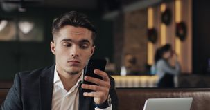 Young businessman working on smartphone sitting in cozy cafe stock video