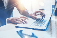 Young businessman working at sunny office on laptop.Man pointing notebook keyboard.Blurred background.Sunlight effects. Royalty Free Stock Photography