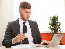 Young businessman working with tablet. And drinking coffee Royalty Free Stock Images