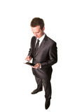 Young businessman working on a tablet pc comuter. Isolated on white Stock Photos