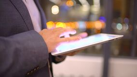 Young businessman working with tablet standing by window in office at night. Close up. slow-motion. Businessman using tablet computer by window in office at stock video