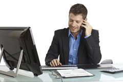 Young businessman working and talking on phone. Young businessman sitting at desk, talking on mobilephone, typing on keyboard, smiling Royalty Free Stock Images