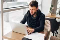A young businessman works in a cafe with a laptop. Businessman in a coffee shop reading a contract document. business executive sitting at cafe working Stock Photo