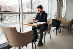A young businessman works in a cafe with a laptop. Businessman in a coffee shop reading a contract document. business executive sitting at cafe working Stock Image